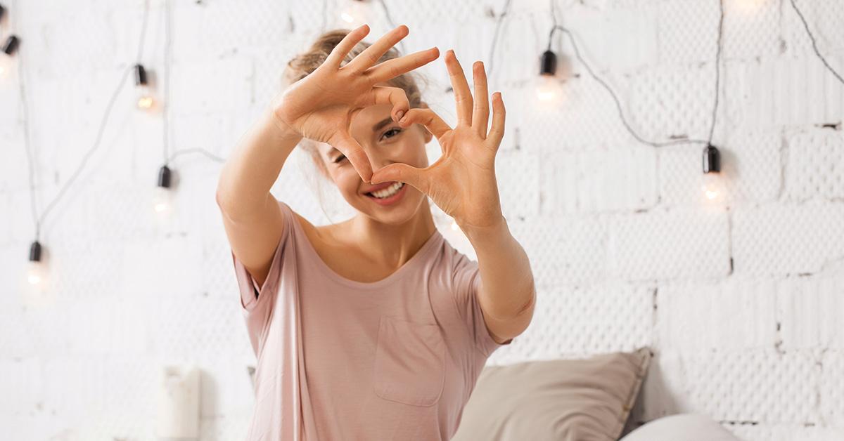 woman making fingers into heart shape