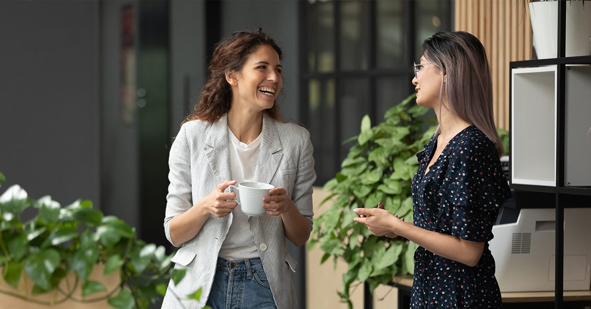 2 women chatting at work. One woman holding a cup of coffee