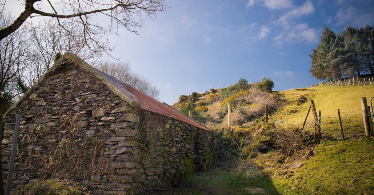 An old stone cabin an a hillside
