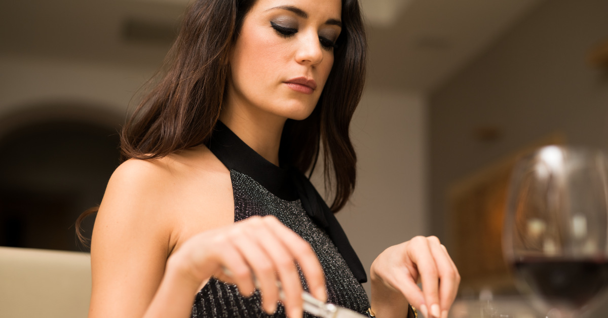 woman in black dress using cutlery sitting down at a dinner table