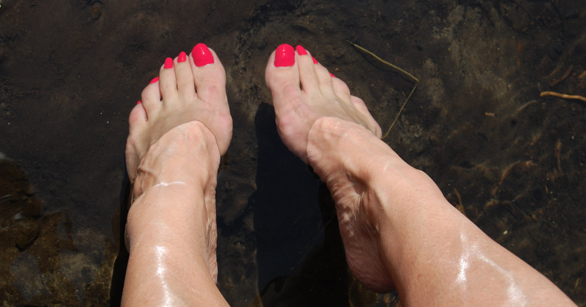 two feet with painted toe nails in water