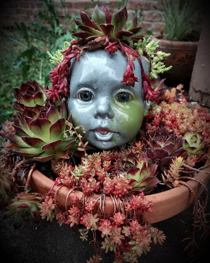 Painted doll head planters succulent arrangement.