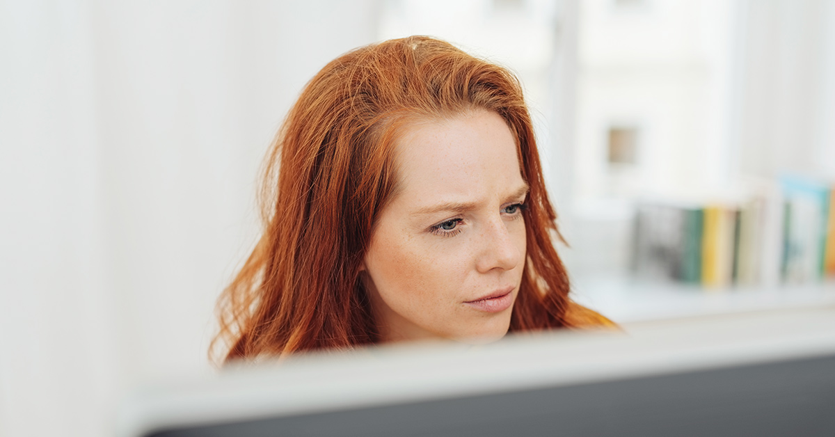 red headed woman who appears to be looking at a computer monitor