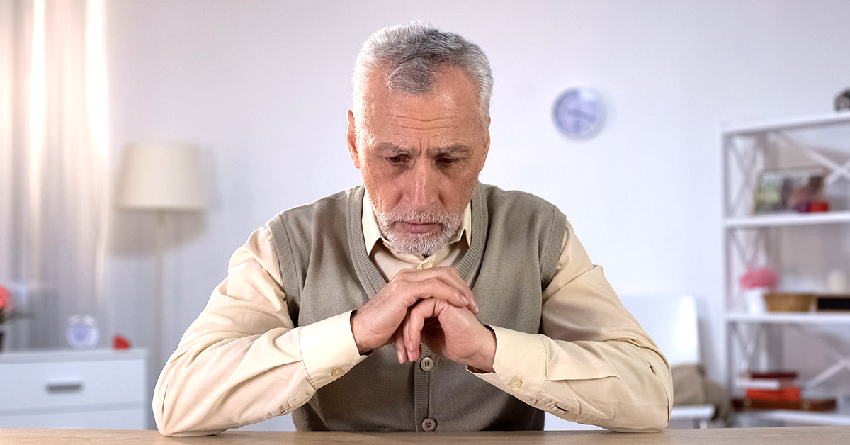 elderly man with hands clasped just under chin concentrating