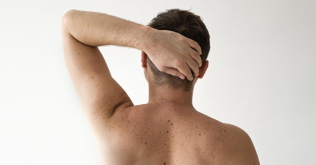 shirtless man seen from behind with arm raised with hand behind his head
