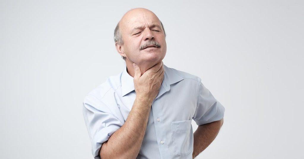 man holding throat