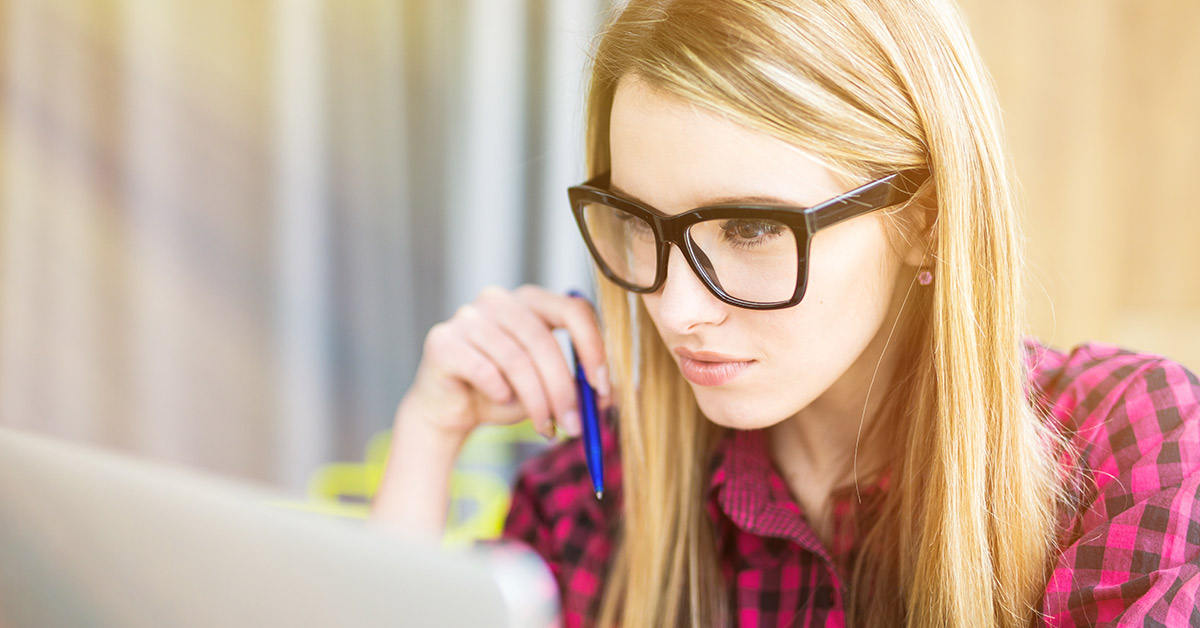 blond woman with thick black framed glasses pondering while using a computer