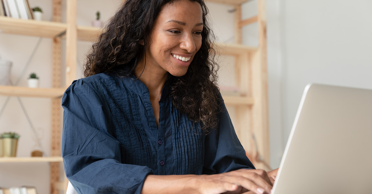 woman smiling and looking at laptop