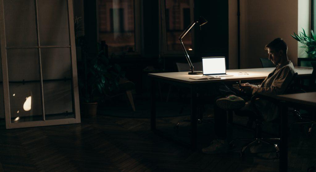 man sitting at desk at night