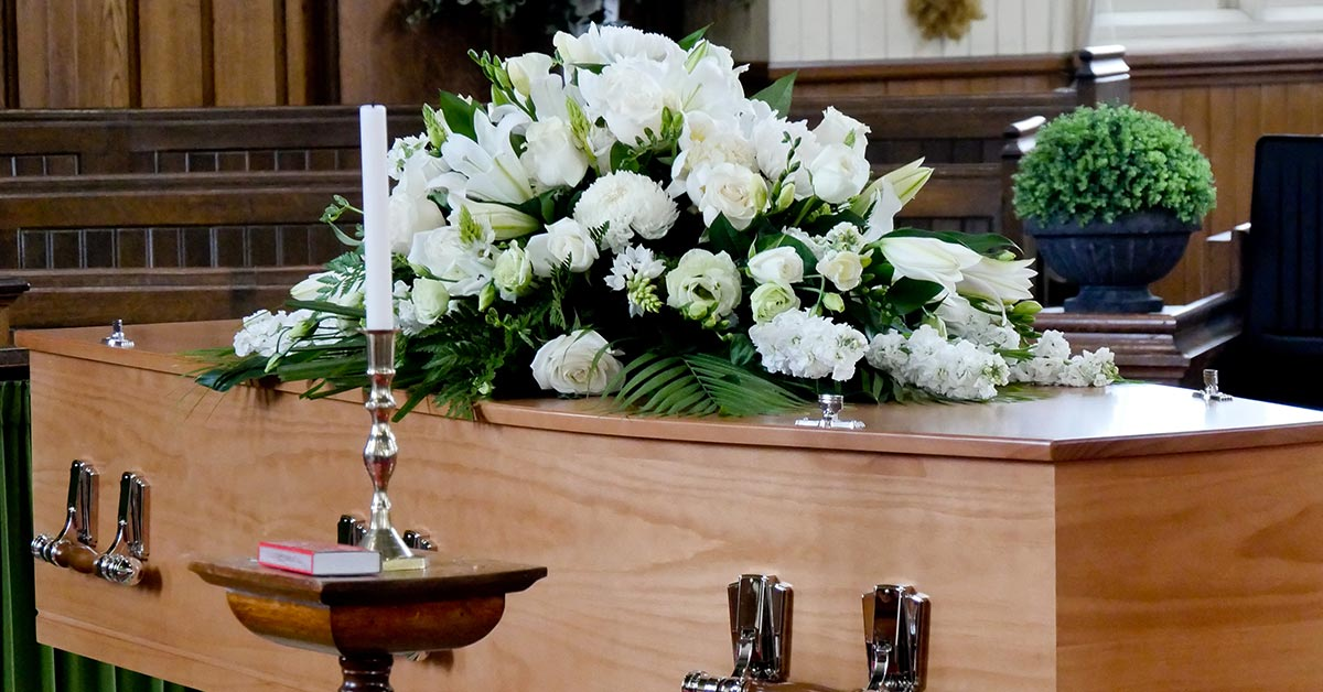 casket with white flowers placed on it at a funeral