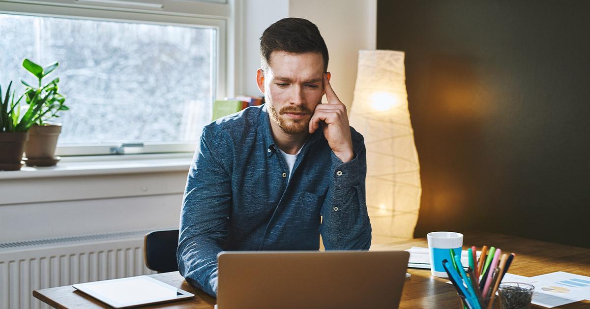 pondering man using laptop