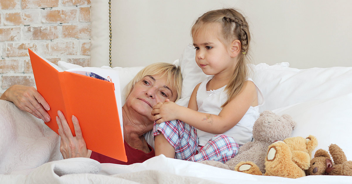 grandparent with grandchild reading a story in bed